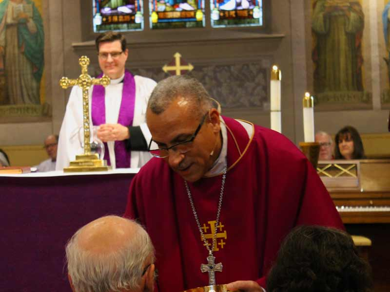 Bishop Fenty delivering communion, Father Dan smiling in the background.